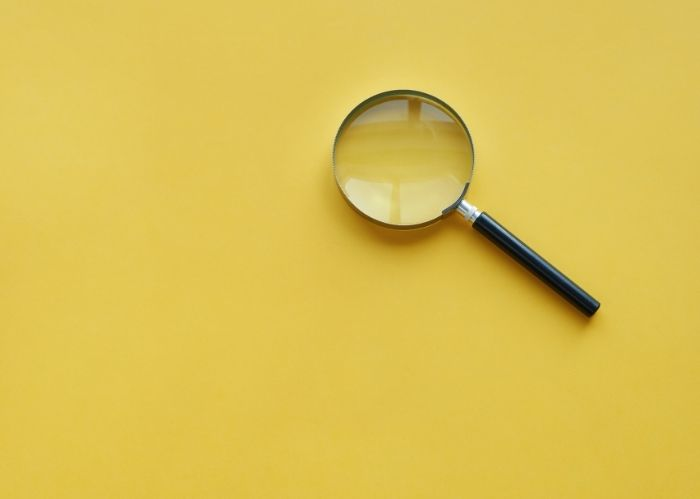 A magnifying glass on a yellow background