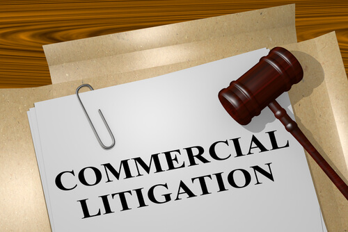 document with the words commercial litigation on a desk with a gavel