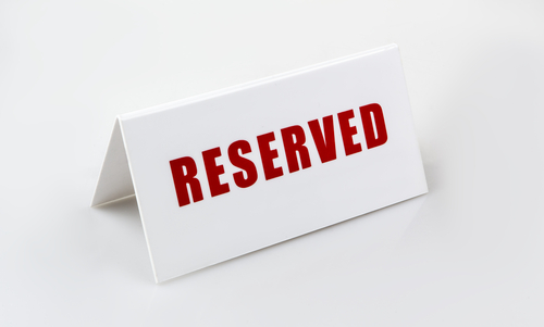 table name badge with the word reserved in red capital letters