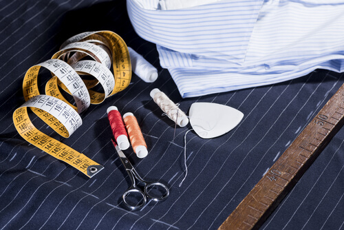a tailors sewing kit on a pin stripe suit and shirt