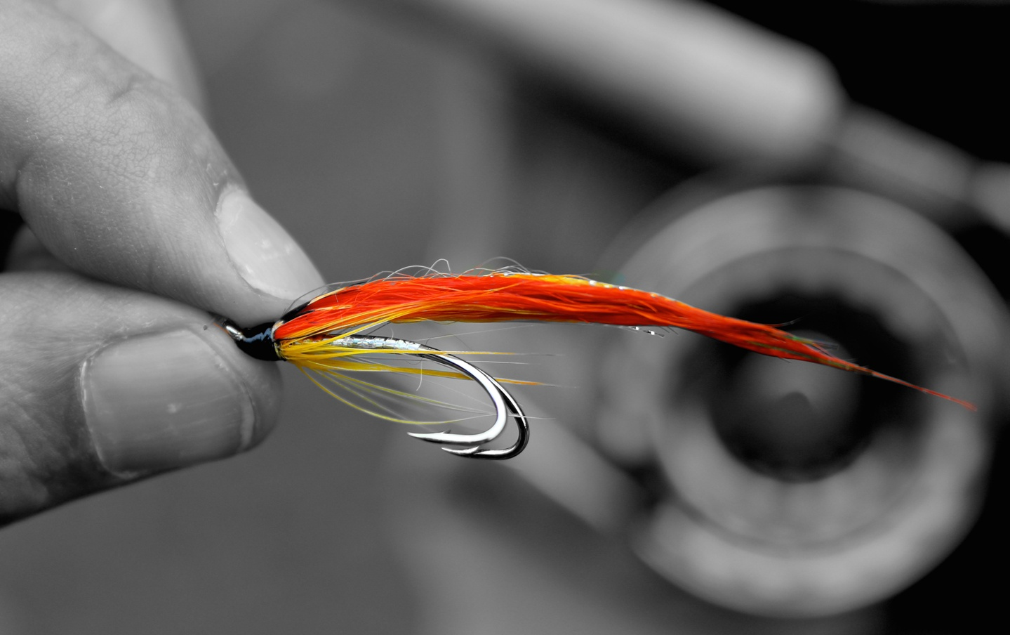 an orange fishing fly held between fingers