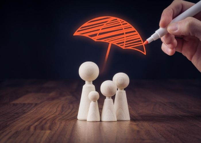 wooden figures under an umbrella
