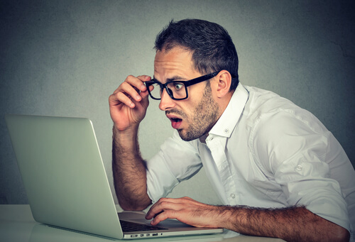 man in glasses with a shocked look on his face staring at computuer screen